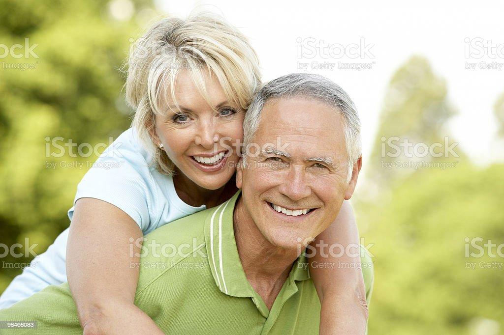 Senior man giving senior woman a piggyback ride royalty-free stock photo