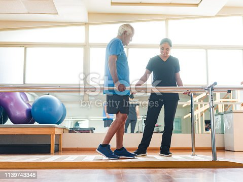A senior man giving small steps in the parallel bars and physical therapist standing next to him.