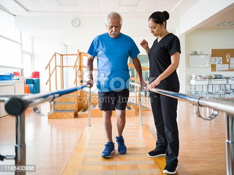 A senior latin man giving some steps with support of the parallel bars.