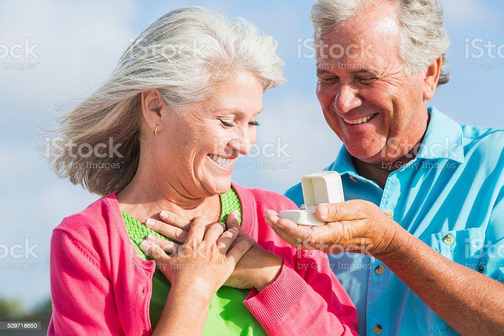 Senior man giving wife an anniversary gift stock photo