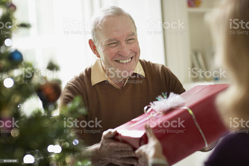 Senior man giving wife Christmas gift royalty-free stock photo