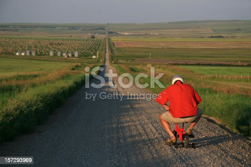 A man goes for a bike ride - but isn't going very far, very fast. Caucasian senior male going for a bicycle ride in a rural setting on a tiny children's bike. Humour. Additional themes include awkward, weird, strange, funny, cute, transportation, driving, cycling, country, dumb, idiot, and stupidity.