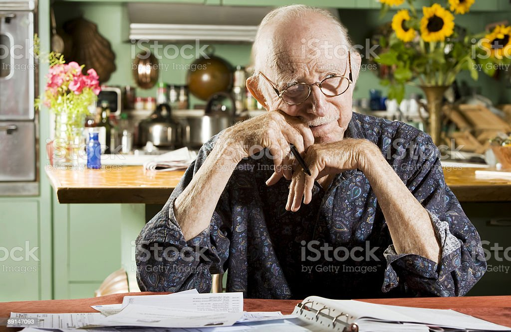 Senior man going over finances with worried expression royalty-free stock photo