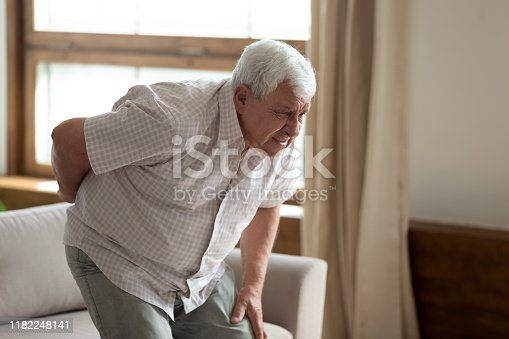 821012164istockphoto Senior man got up from couch felt low back pain 1182248141