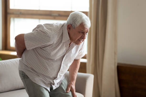 Senior man got up from couch felt low back pain Senior grey haired 70s years man got up from couch writhes in pain felt sharp ache suffers from low back strain, touch loin reduce backache. Degenerative disk disease, pinched nerve rheumatism concept dorsal surface stock pictures, royalty-free photos & images