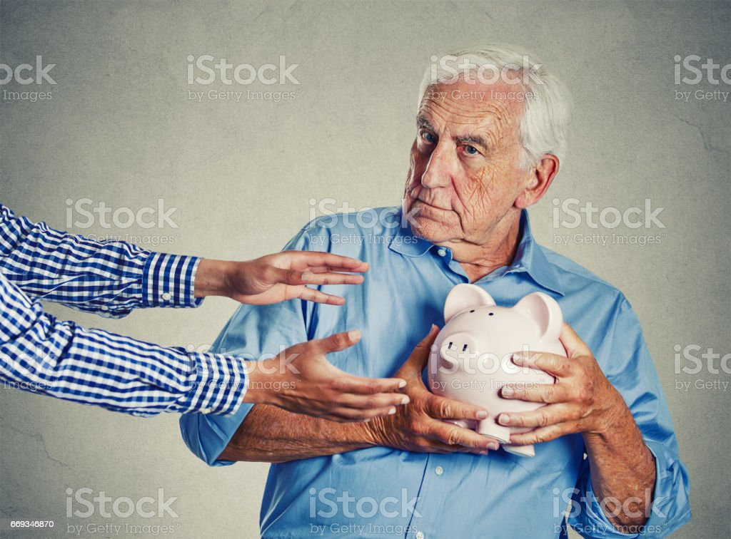 senior man grandfather holding piggy bank looking suspicious trying to protect his savings from being stolen stock photo