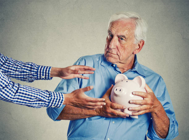 senior man grandfather holding piggy bank looking suspicious trying to protect his savings from being stolen - investment fraud stock pictures, royalty-free photos & images