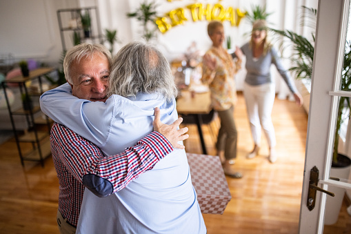 Senior man greeting his friend who's coming with present on birthday party