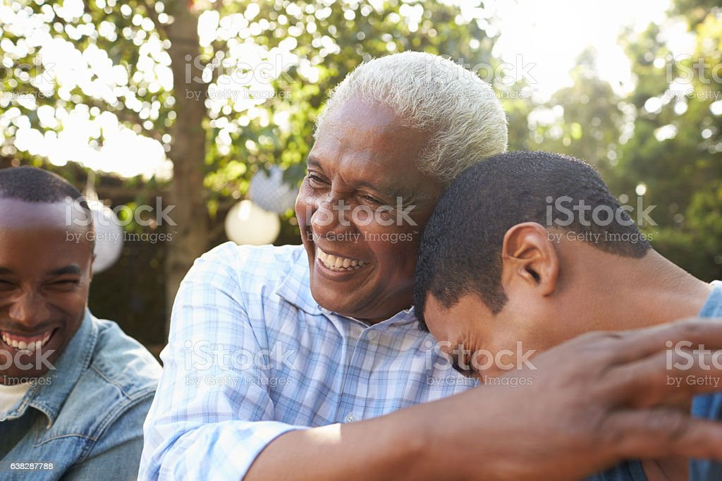 Senior man greeting his two adult sons in garden, stock photo