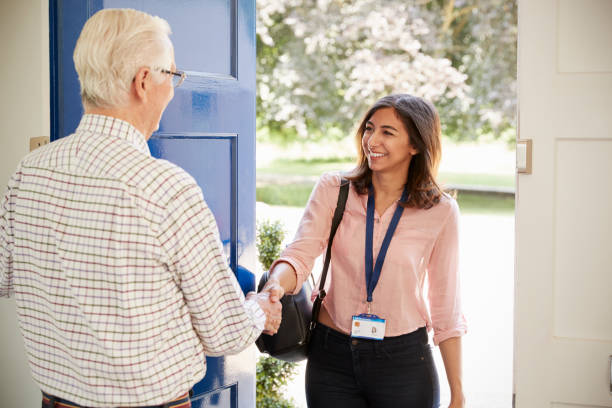 senior man greeting young woman making home visit - healthcare worker stock photos and pictures