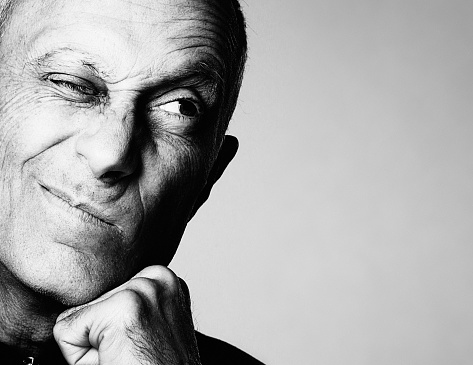 A good-looking older man resting his chin on his hand grimaces, screwing up one eye and looking to the side, where there is copy space, in irritated disbelief. Black and white image.