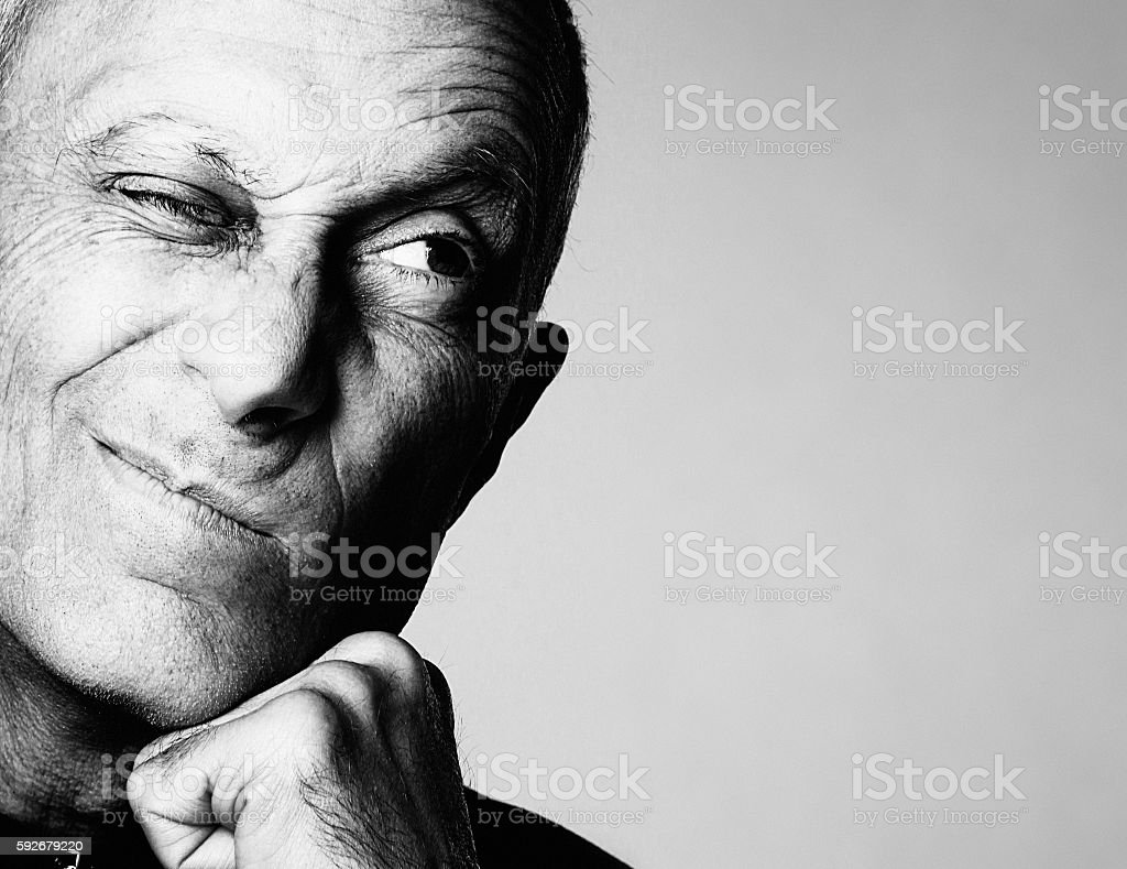 Senior man grimaces cynically looking to the side stock photo
