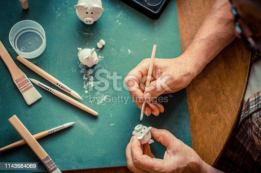 Senior man creating little clay pigs.