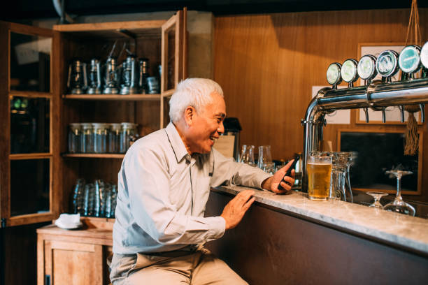 Senior Man Hangout Drinking beer in Pub Image of Senior Man Hangout Drinking beer with mobile phone in Pub. old man working in a pub stock pictures, royalty-free photos & images