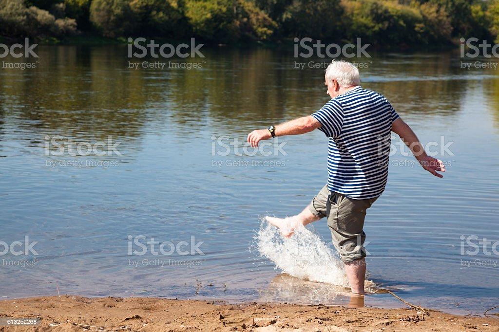 senior man has fun paddling and splashing in river stock photo