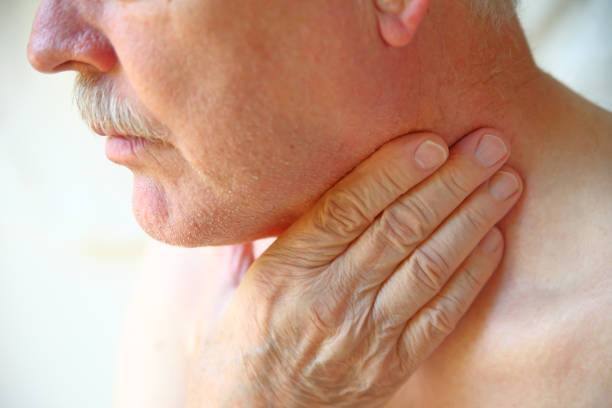 Senior man has hand on throat Older man with his hand against his throat, natural light respiratory disease stock pictures, royalty-free photos & images