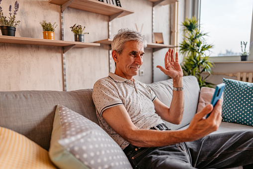 Senior man relaxing on sofa at home and making a video call on smartphone.