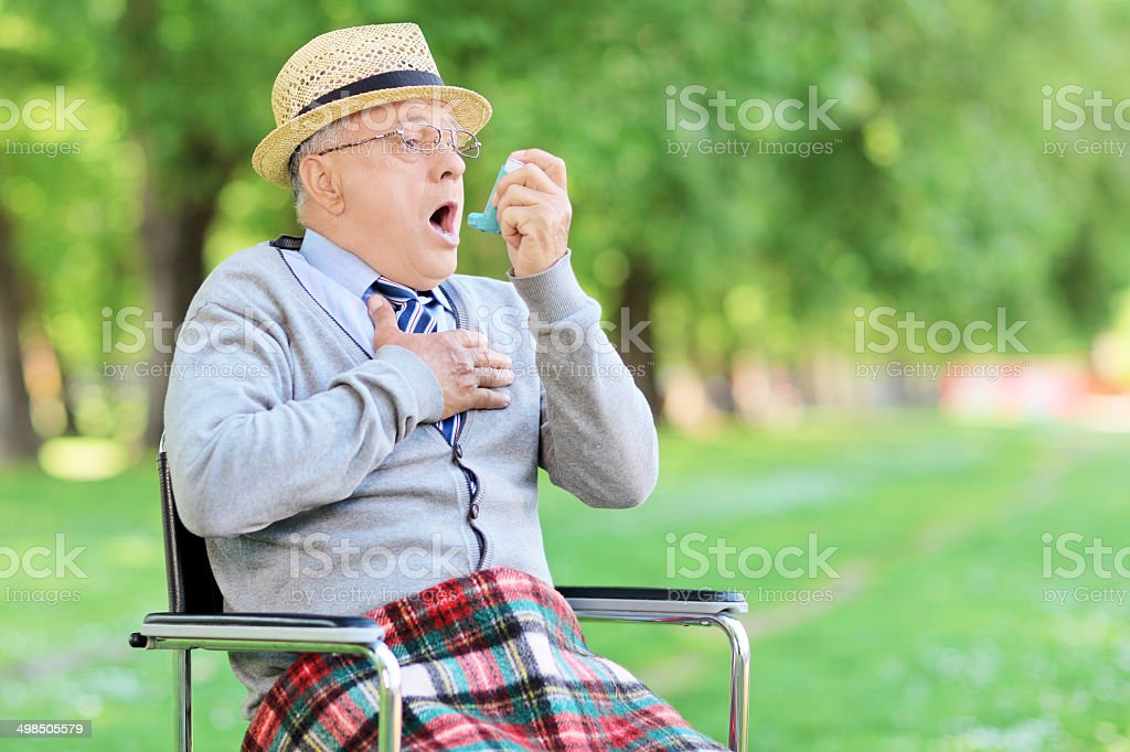 Senior man having an asthma attack in park stock photo