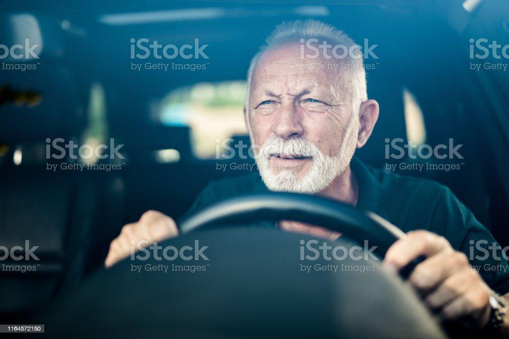 Senior man having bad eye sight and making effort to see the road.