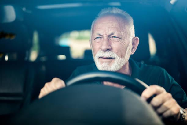 senior mann mit schlechten augen und bemühungen, die straße zu sehen. - berufsfahrer stock-fotos und bilder