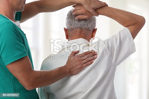 istock Senior man having chiropractic back adjustment. Osteopathy, Physiotherapy, pain relief concept 854656852
