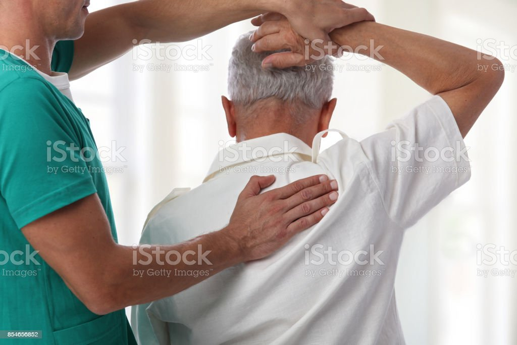 Senior man having chiropractic back adjustment. Osteopathy, Physiotherapy, pain relief concept stock photo