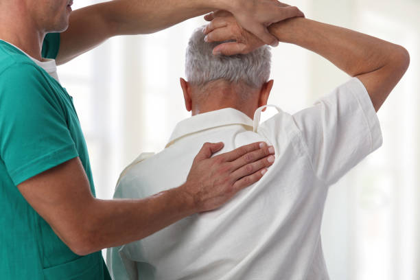 Senior man having chiropractic back adjustment. Osteopathy, Physiotherapy, pain relief concept - foto stock
