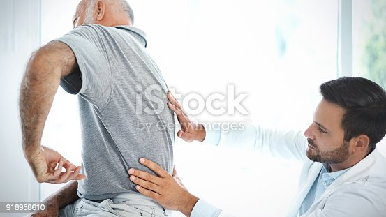 885281276istockphoto Senior man having his back examined by a doctor. 918958610