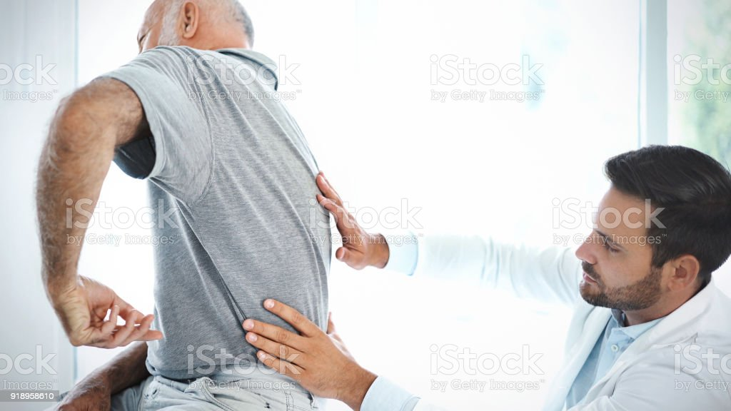 Senior man having his back examined by a doctor. stock photo