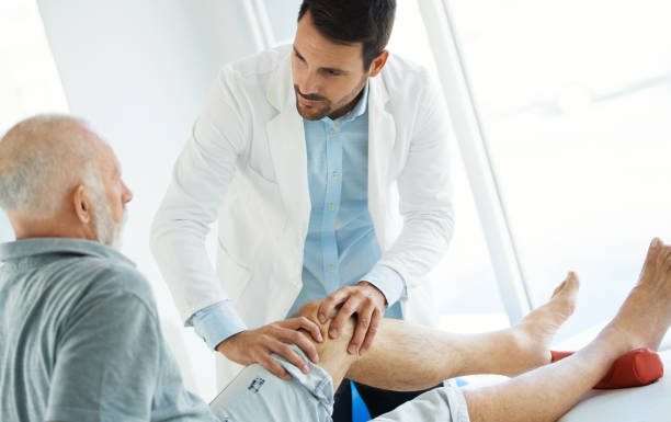 senior man having his knee examined by a doctor. - ginocchio foto e immagini stock