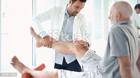 Closeup side view of early 30's doctor examining a knee of a senior gentleman during an appointment. The doctor is gently touching the tendons around the knee and the knee cap and trying to determine the cause of pain.