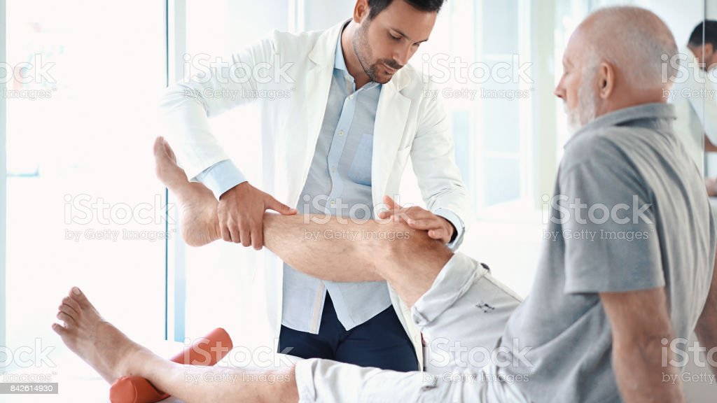 Senior man having his knee examined. stock photo