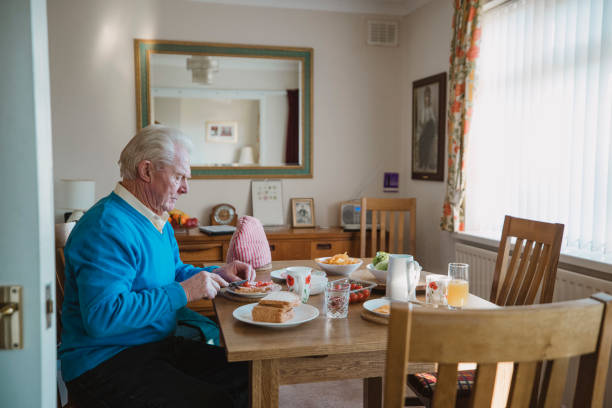 Senior Man Having Lunch One senior man is sitting at the dining table in his home having lunch. He is making a ham salad sandwich. one senior man only stock pictures, royalty-free photos & images
