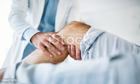 Closeup side view of early 30's unrecognizable doctor examining a knee of a senior gentleman during an appointment. The doctor is gently touching the tendons around the knee and the knee cap and trying to determine the cause of pain.