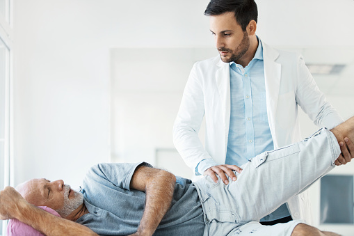 Closeup side view of early 30's doctor examining a hip of a senior gentleman during an appointment. The doctor is gently lifting patient's leg sideways