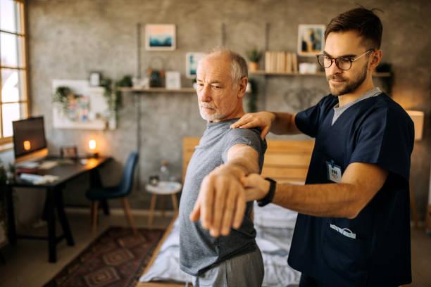 Senior man having physical therapy at home stock photo