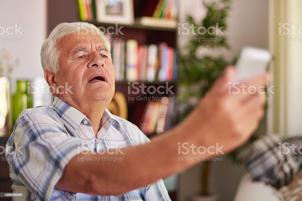 Senior man having problem with his eye sight stock photo