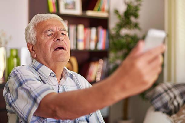 Senior man having problem with his eye sight stock photo