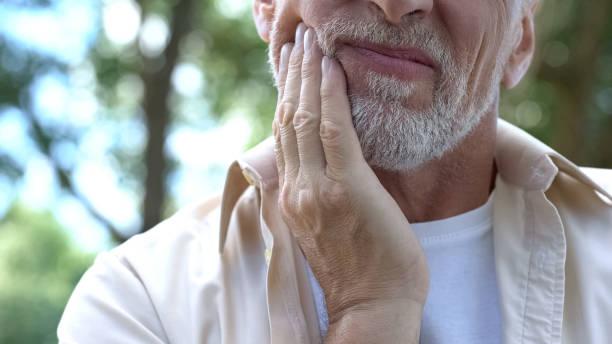 Senior man having problem with teeth, social program of dental prosthetics stock photo