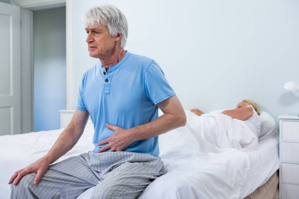 Senior man having stomach pain while sitting on bed stock photo