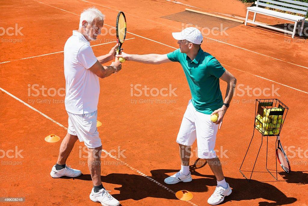 Senior man having tennis lesson stock photo