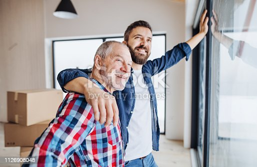 istock A senior man helping his son with furnishing new house, a new home concept. 1126908048