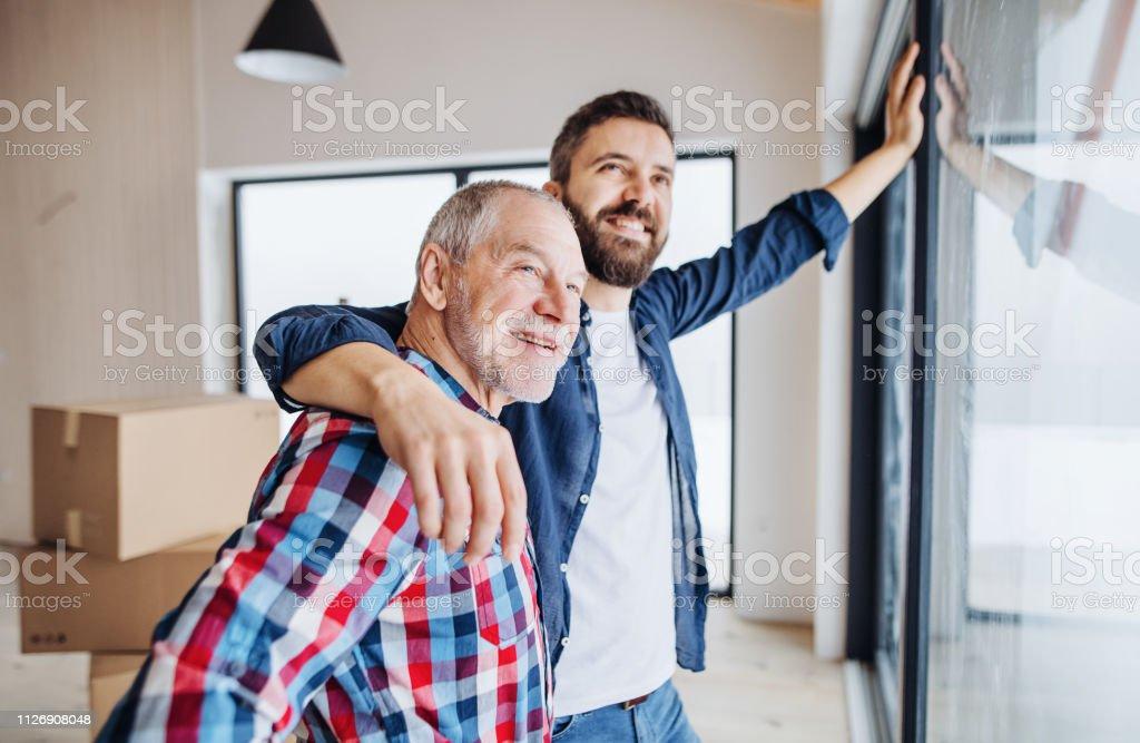 Ein senior Mann seinen Sohn mit Einrichtung neues Haus, ein neues Wohnkonzept zu helfen. – Foto
