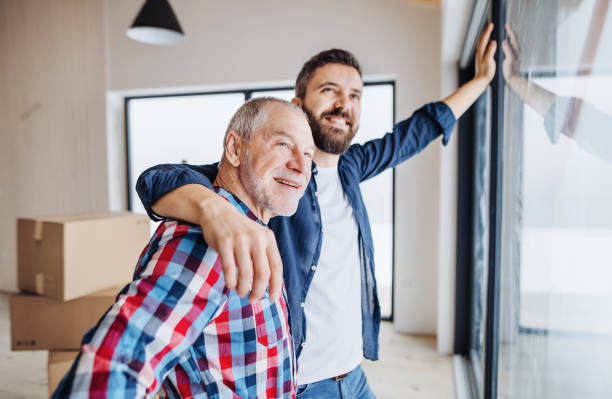 A senior man helping his son with furnishing new house, a new home concept. stock photo