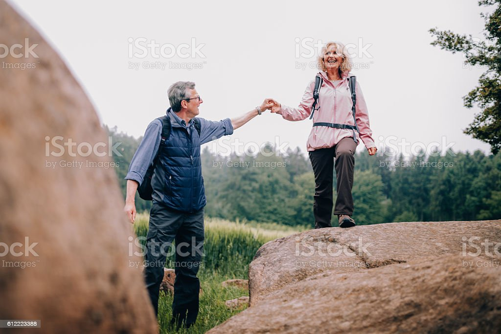 Senior Man helping his wife climbing up a rock on stock photo