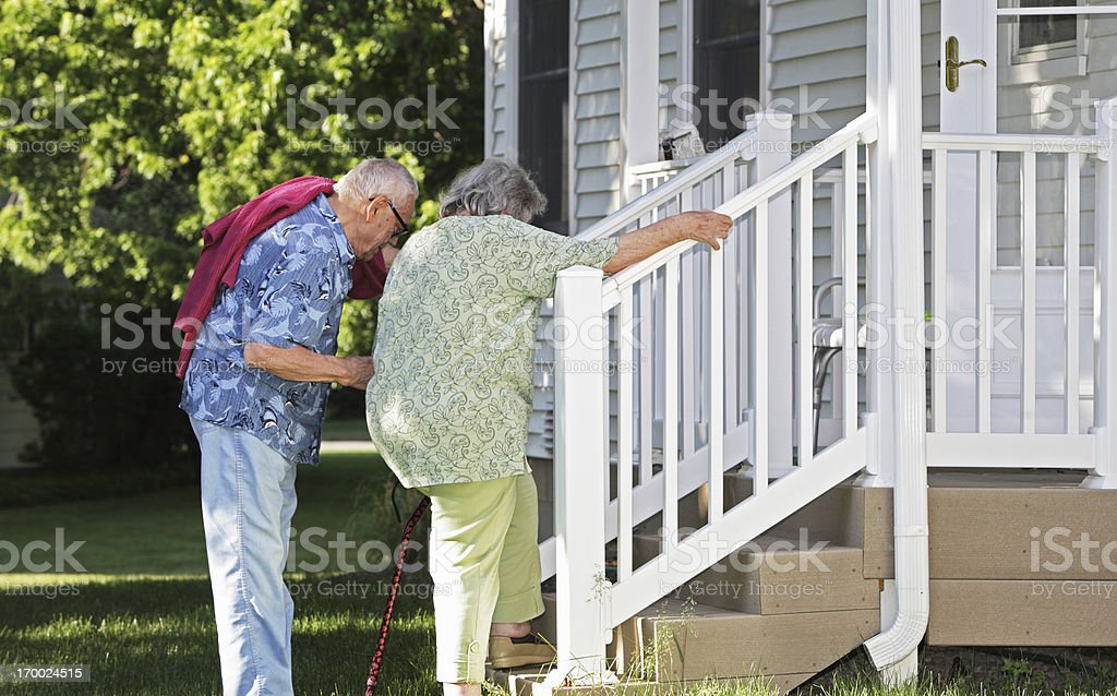 Senior Man Helping Wife Climb Stairs stock photo