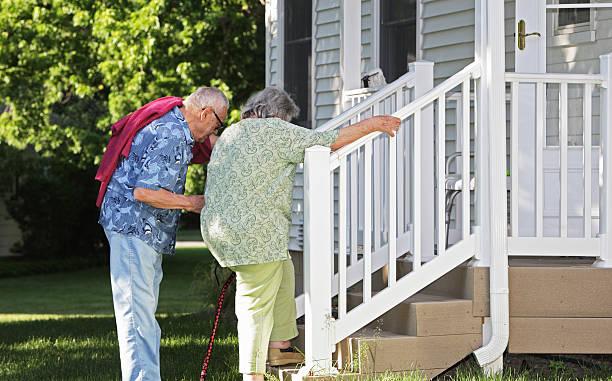 senior man helping wife climb stairs - mänsklig bosättning bildbanksfoton och bilder