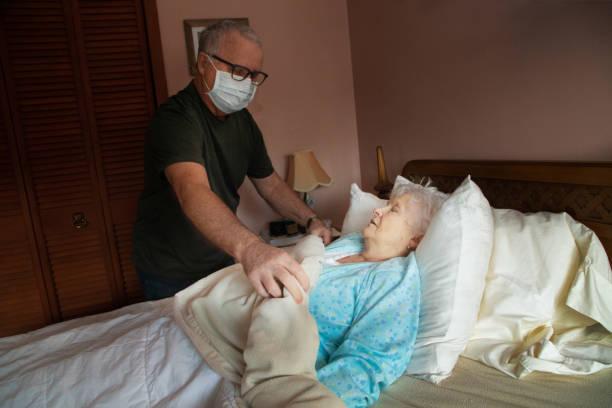 Senior Mann hilft, kranke ältere Frau im Bett zu trösten – Foto