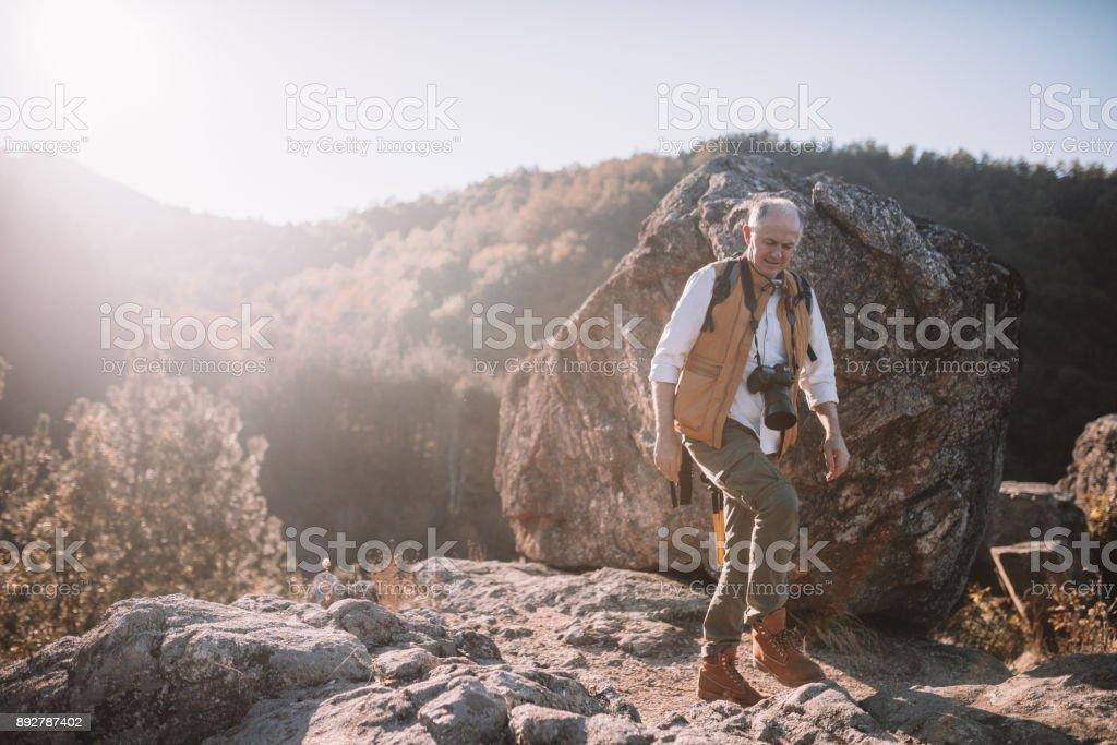 Senior man hiking on a mountain track stock photo