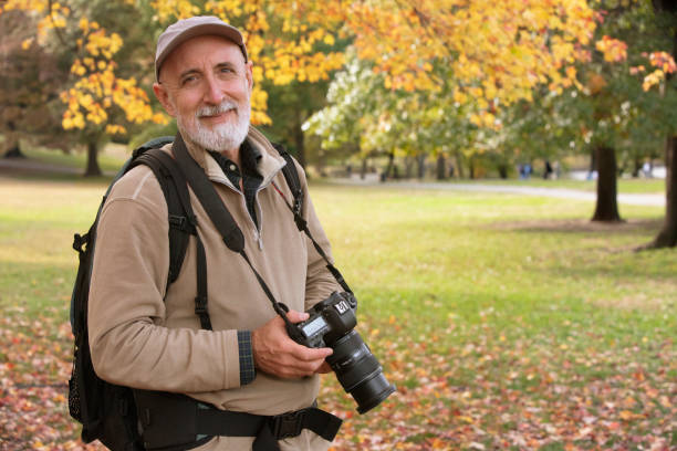 Senior man hiking outside in nature and taking pictures